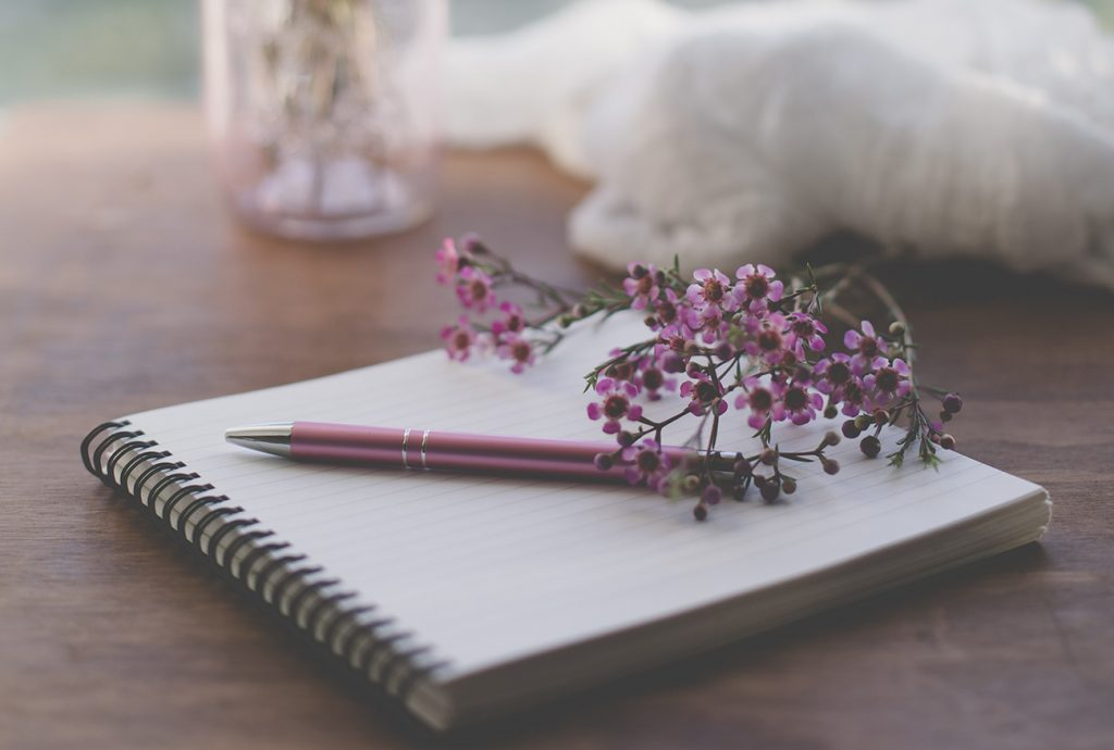 Pen and flowers on top of a notebook